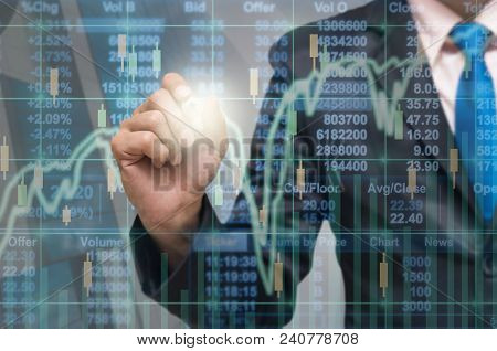 Businessman Writing The Trading Graph Of Stock Market On The Virtual Screen On Photo Blurred Of City