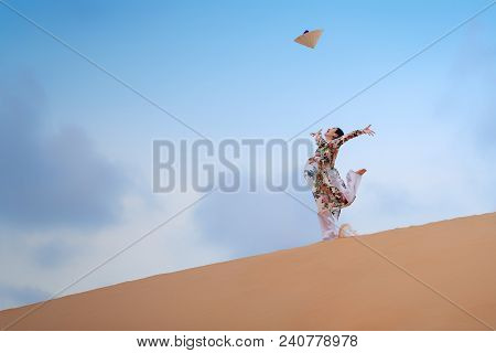 Young Vietnam Woman Wearing Ao Dai Culture Traditional Jumping On The Desert At Muine In Vietnam,vin