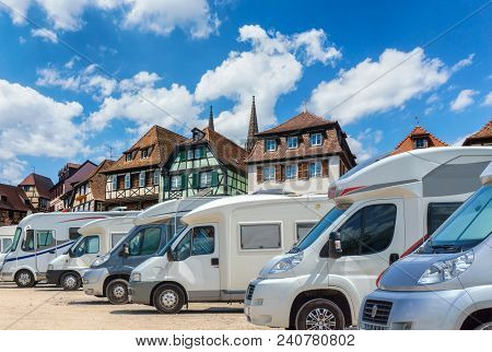 Close up motorhomes parked in a row on background traditional colorful houses in La Petite France, Strasbourg, Alsace, France poster