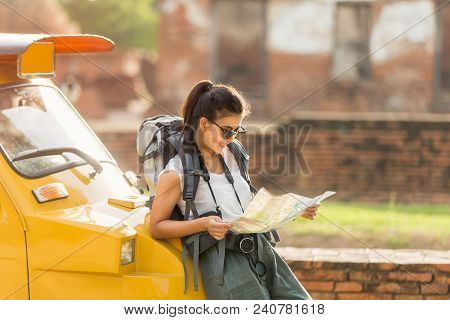 Young Asian Female Traveler With Backpack Traveling Standing On Taxi Or Tuk Tuk And See Map Travel W