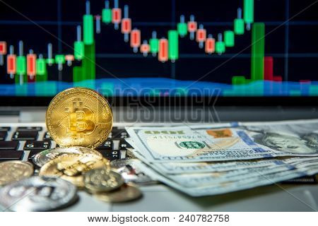 Studio Shot Of Bitcoin Gold Silver Coins And Dollar Bank Note On Laptop Keyboard With Basic Candlest