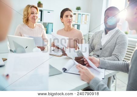 Group of financial managers in casualwear gathered together at modern boardroom and preparing annual accounts, lens flare