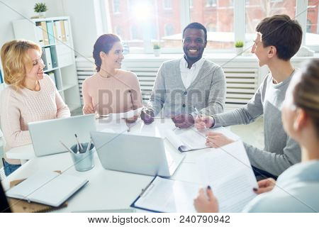 Handsome African American manager looking at camera with toothy smile while participating in working meeting at spacious boardroom, lens flare
