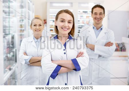 Welcome In Drugstore. Jolly Three Pharmacists Crossing Arms While Staying In Drugstore