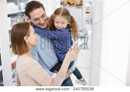 Local Drugstore. Jovial Jolly Woman Selecting Drug While Man Holding Girl