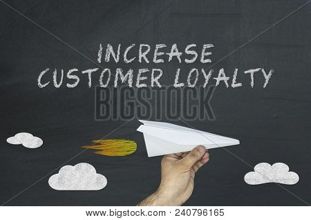 Increase Customer Loyalty Concept On Blackboard. Hand Holding Paper Plane