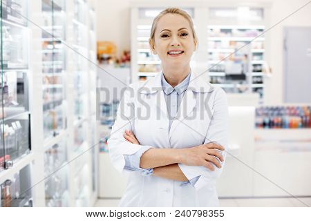 Perfect Pharmacist. Joyful Female Pharmacist Crossing Hands And Posing On Blurred Background