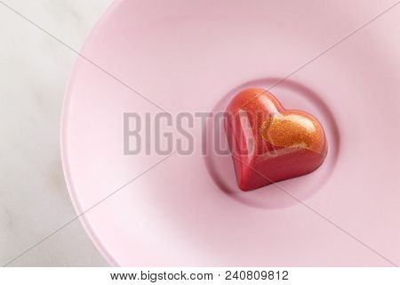 Red Heart Shaped Handmade Chocolate Candy On Pink Plate. Exclusive Handcrafted Bonbon. Luxury Exclus