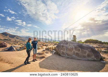 Couple Of Tourist Near Ancient Stone Painting