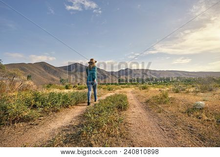 Woman In Hat And Green Checked Shirt Walking On Country Road Near The Farm At The Morning