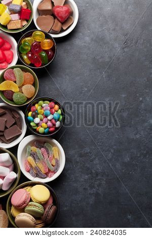 Colorful sweets. Lollipops, macaroons, marshmallow, marmalade and candies. Top view with space for your greetings