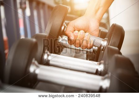 Close Up Of Man Holding Rows Of Dumbbells In The Gym.gym Equipment And Sport Concept.
