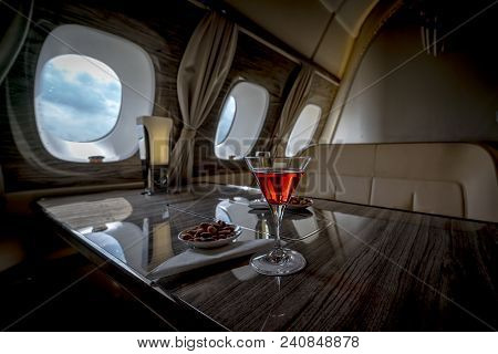 Interior Of A Business Class Of A Commercial Passenger Plane, An Armchair And A Window, A Table And