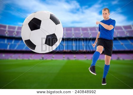 Young Soccer Player In Blue Uniform Kicking Ball Over Stadium Background