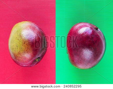 Red And Green Mango Fruits On The Corrugated Paper Of Opposite Color Background.