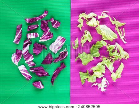 Bright Purple And Green Lettuce Salad Leaves On The Corrugated Paper Of Opposite Color Background.