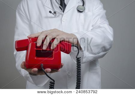 Medical Call Center Operator In Medical Clinic. Unrecognizable Male Doctor With Red Phone.