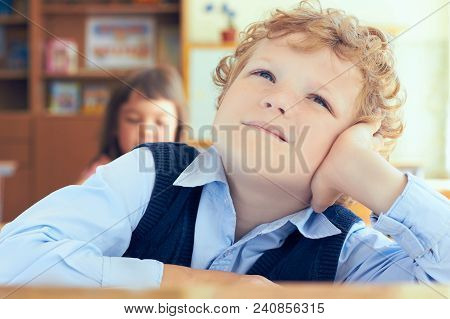 Portrait Of Cute Thoughtful Schoolboy Sitting At The Desk And Dreaming