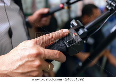 Close-up of working camera of man hand, operator at work. Stock photo poster