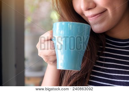 Closeup Image Of A Beautiful Asian Woman Smelling And Drinking Hot Coffee With Feeling Good In Cafe