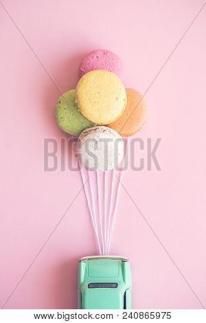 Small Retro Car Attached To Colorful Macaroons In Form Of Helium Balloons On Pastel Pink Background