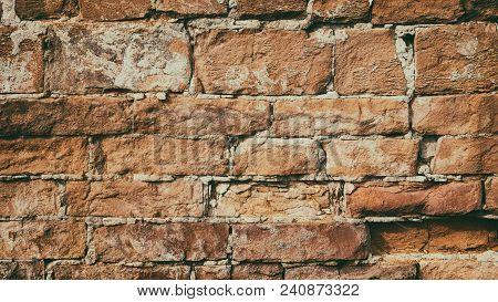 Old Crumbled Orange Brick Wall Texture. Aged Brickwork Masonry. Retro Style Grunge Background