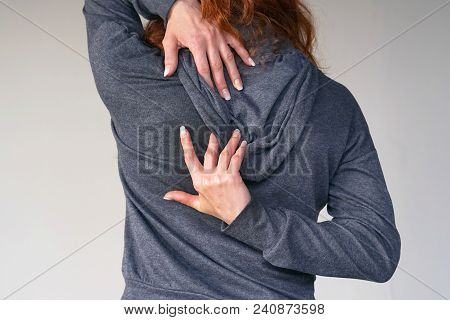 Close-up View Of A Young Woman With Pain In Kidneys Isolated On Gray Background. Young Woman With Ba