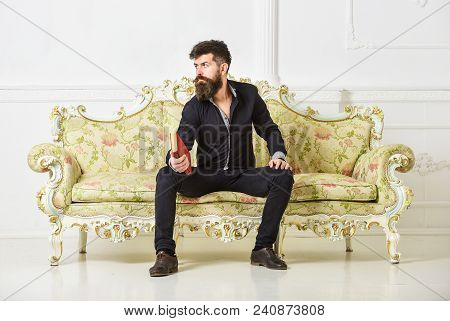 Man With Beard And Mustache Spends Leisure With Book. Lecturer Sit On Sofa And Holds Book, White Wal