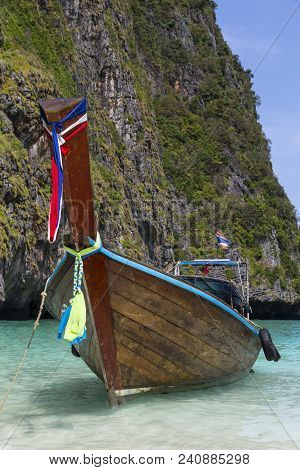 Old Beautiful Traditional Wooden Thai  Longtail Boat On A Sea Surface Against A Rock Background. Tha