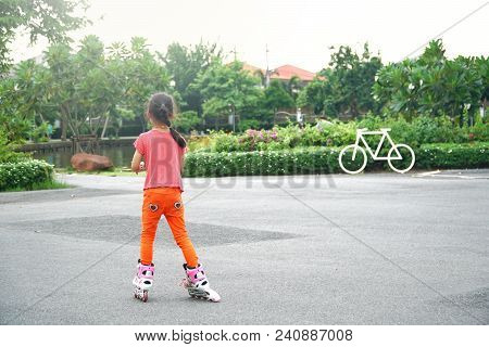 Young Asian Girl Riding On Roller Skates In Public Park Outdoor In The Evening Summer. Funny Child I