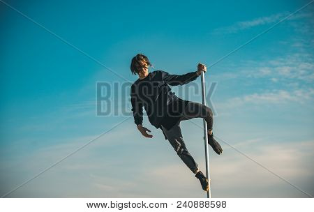 Pole Dance Sport. Sexy Macho Man Fly On Blue Sky Background. Athletic Guy Make Acrobatic Elements On