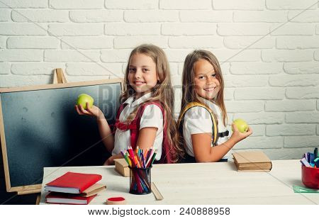 School Time Of Girls. Little Girls Eat Apple At Lunch Break. Back To School And Home Schooling. Frie