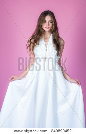 Fashion model or princess at prom. Wedding fashion and beauty salon. Bride girl at wedding ceremony. Sexy girl in white dress with stylish hair. Woman on pink background in summer dress. poster