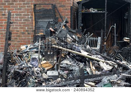 Garden Shed Fire Damage. Pile Of Charred Melted And Burnt Remains From Serious House Garden Fire.