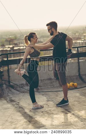 Young Couple On A Building Rooftop Terrace Stretching Before Workout; Urban Skyline In The Backgroun