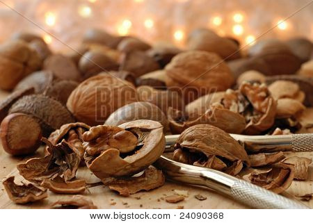 Holiday background image with mixed nuts and nutcracker on wood surface against  background of defocused golden lights   Macro with extremely shallow dof.