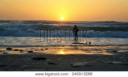Surfs Up California. A Man In A Wet Suit Walking Into The Ocean Sunset.