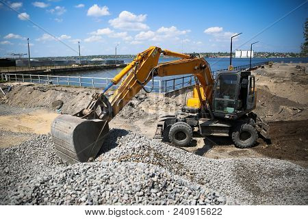 Big Excavator On New Construction Site. Excavator Loader Machine During Earthmoving Works Outdoors A