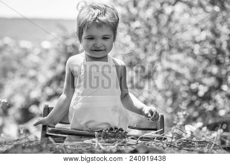 Cute Little Boy In White Pinafore Eats Fruit Cake On High Chair At Table On Sunny Summer Day On Natu