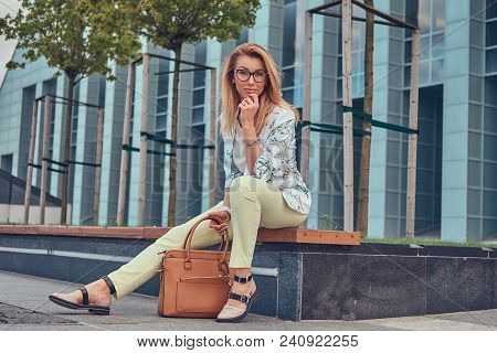 Charming Fashionable Woman In Stylish Clothes And Glasses With A Handbag, Sitting On A Bench Against