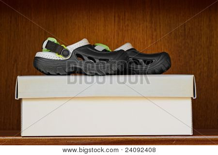 fun kid rubber slip on sandals with rubber sole on a box in a wooden shelf display with copy space