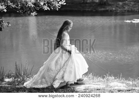 small girl kid with long blonde hair and pretty smiling happy face in prom princess white dress standing sunny day outdoor near water poster