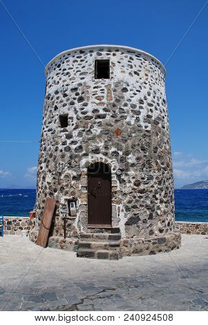 An old stone windmill on the seafront at Mandraki on the Greek island of Nisyros.
