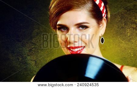 Retro woman with music vinyl record. Pin-up retro female style. Pin-up portrait of girl style wearing red dress. Sale of antiques. Texture of old wall in background.