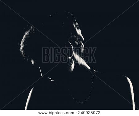 Silhouette of head woman in little black cocktail dress with bare shoulders on black background. Female portrait in profile with evening hairstyle and jewelry. Photo of black and white photo with soft