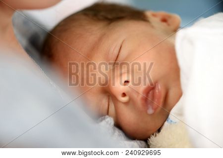 Newborn baby boy with milk drop in his mouth closeup. Breastfeeding and motherhood concept