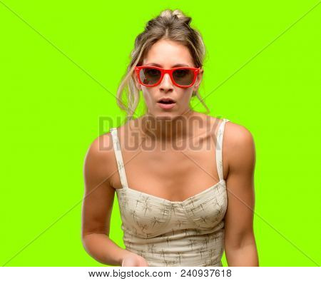 Young beautiful woman wearing red sunglasses scared in shock, expressing panic and fear