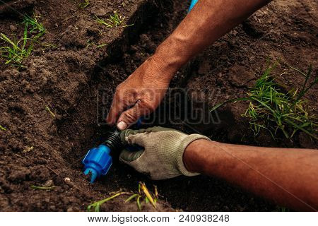 Watering System For A Garden In The Ground. Worker Joins Pipes