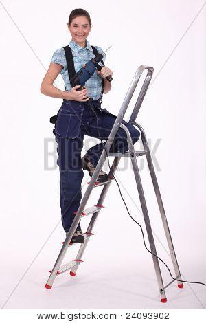 A servicewoman with a driller on a ladder.
