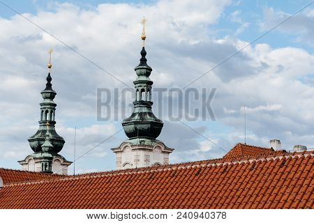 Spires And Roof Of Strahov Monastery In Prague Against Cloudy Sky. Low Angle View